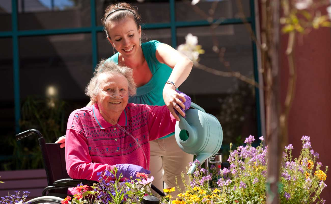 Smiling Scripps stroke rehabilitation therapist helps an elderly woman in a wheelchair water flowers in an outdoor garden setting.