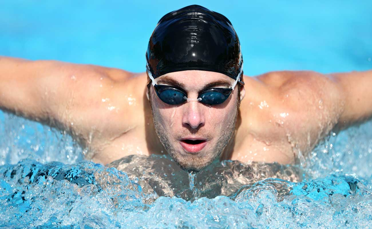 Athletic swimmer wearing a swim cap and goggles in a pool.