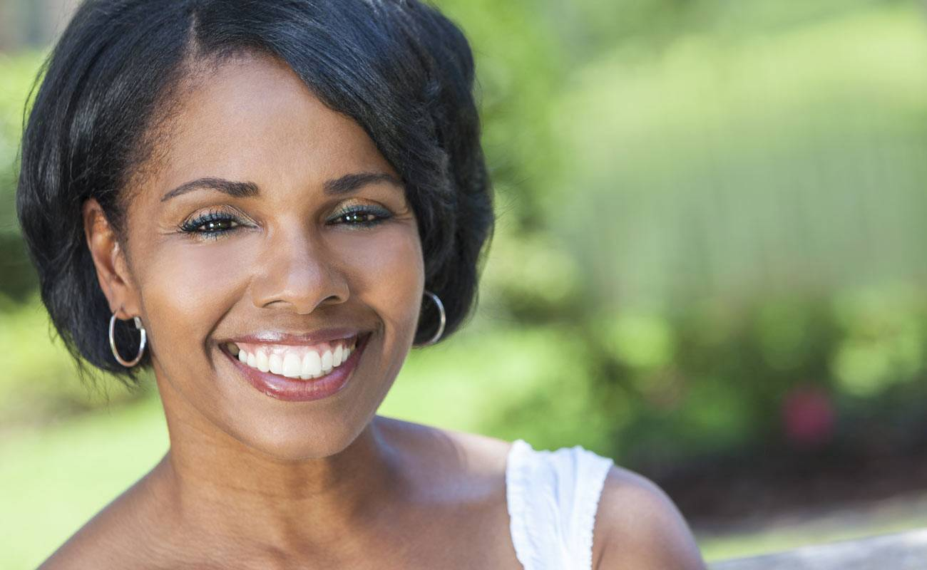 African-American woman with short hair, white dress and earrings smiling with green trees in the background.