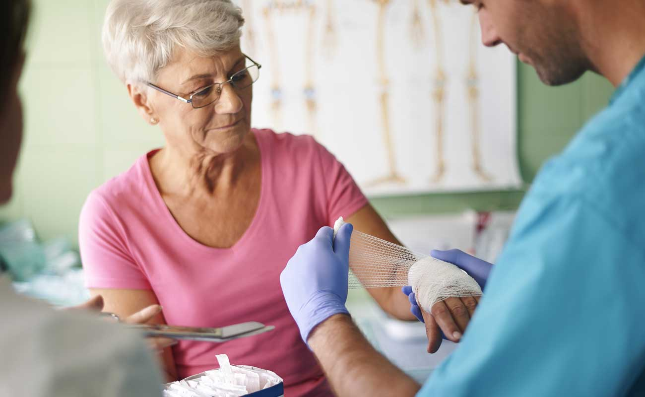 Scripps wound therapy specialist provides treatment to an elderly woman with a hand injury.