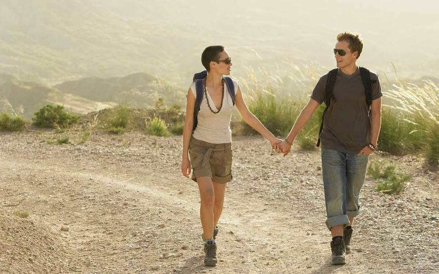 A couple holding hands and walking on a hiking trail.