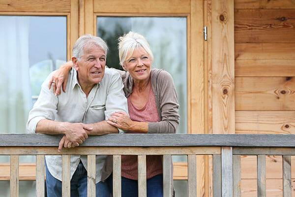 Mature couple standing on cabin deck.