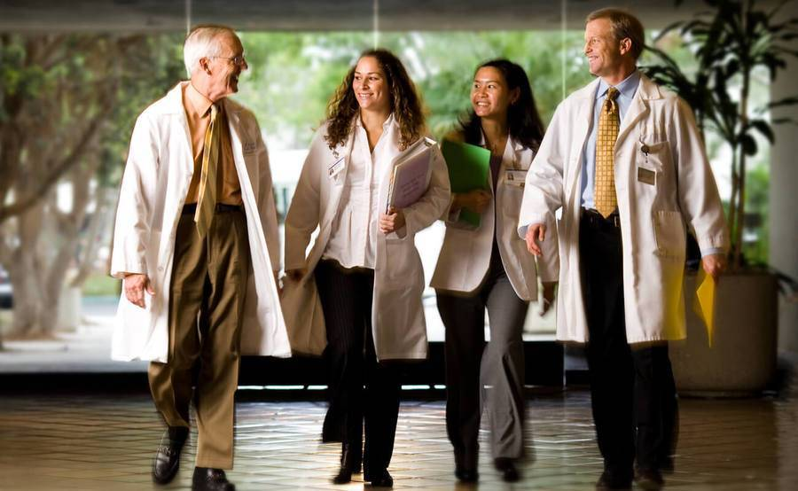 A team of doctors walks down a hallway, representing the expertise of Scripps hip replacement surgeons and physical therapists.