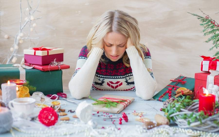 Woman wearing holiday-themed sweater presses her hands against her temples because she's stressed by the holiday season.