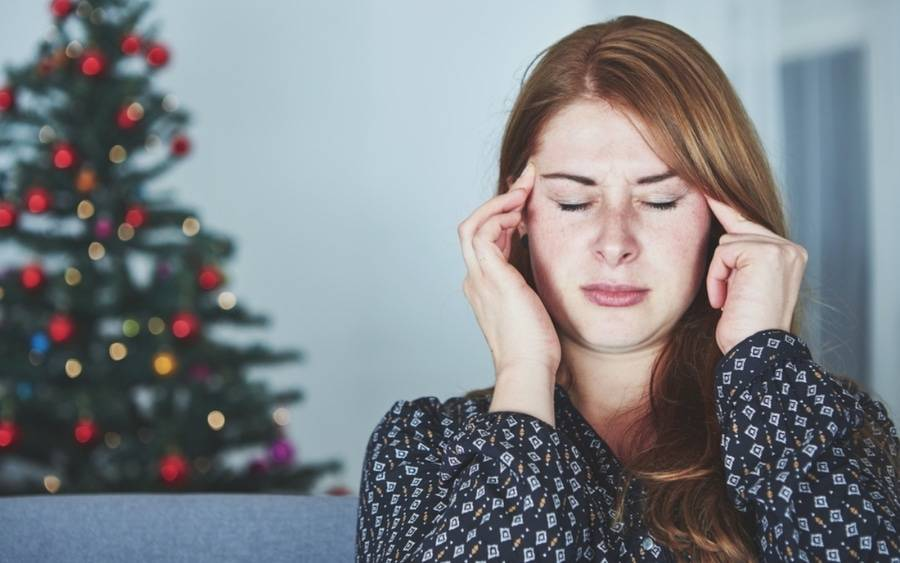Woman touches the temples of her head, stressed from dealing with relatives during the holidays.