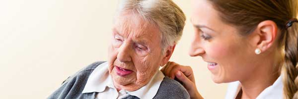 A Scripps home health professional assists an elderly patient with physical therapy treatment in a home environment.