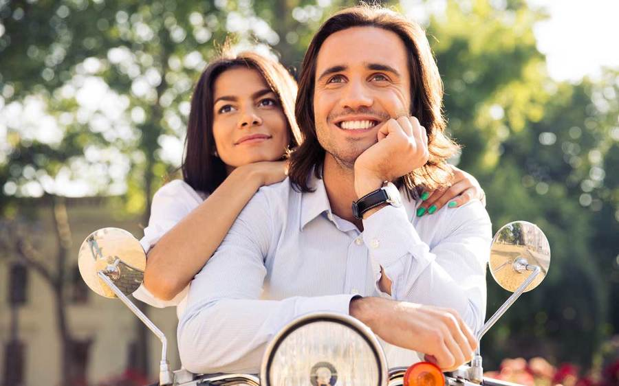 Man and woman smiling thoughtfully while seated on a motorbike in an outdoor setting.