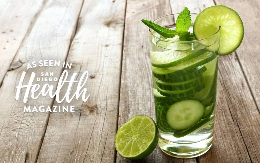 A glass of water with cucumber slices represents the easy ways to enjoy flavored water to help prevent dehydration. As seen in San Diego Health Magazine.