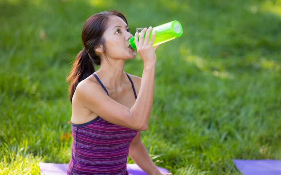 A woman drinking water while on a break from exercising.