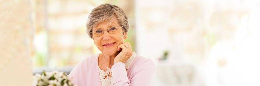 A relaxed elderly woman enjoys a peaceful moment in a pleasant indoor setting.