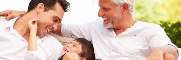 A grandfather, father and son share laughter in a bright outdoor setting.