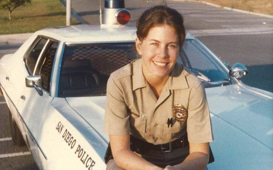 Janet Chelberg-Burgess siiting on the hood of a San Diego Police vehicle, circa 1977.