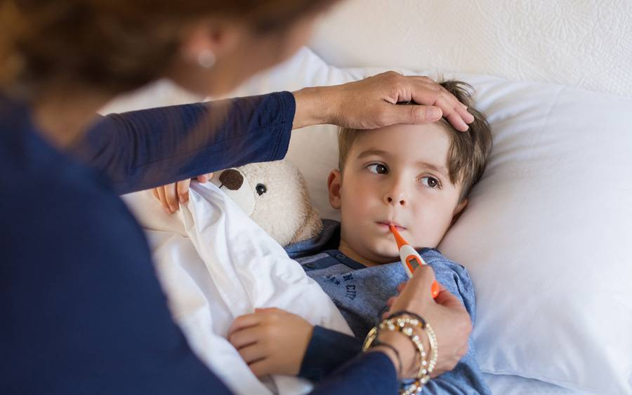 A child with a fever gets his temperature taken.