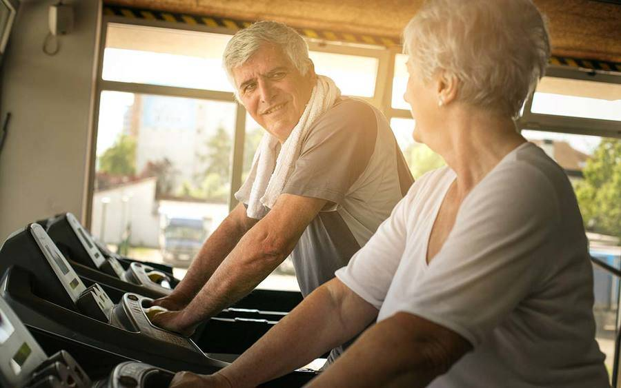 Mature couple working out on treadmmill