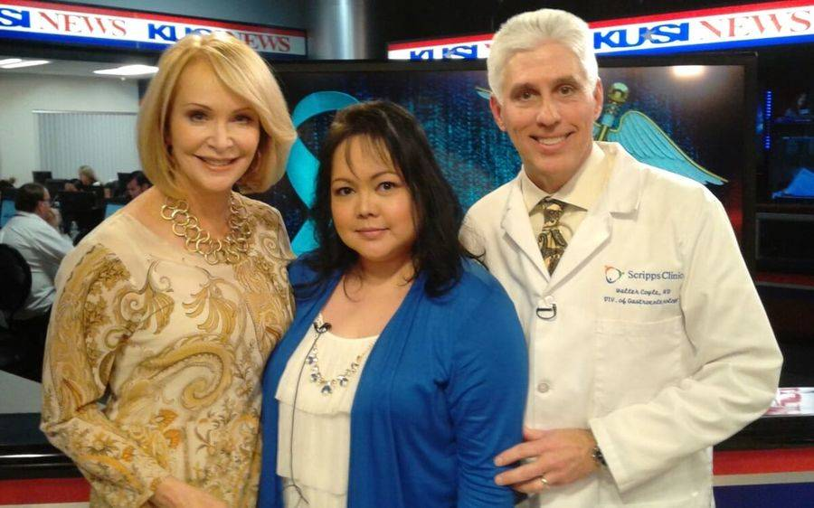 A young woman in a blue sweater who is a Scripps colorectal cancer patient stands with a KUSI news anchor and Scripps doctor.