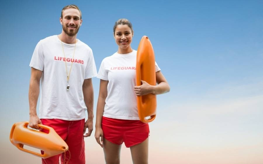 Two lifeguards pose at the beach.