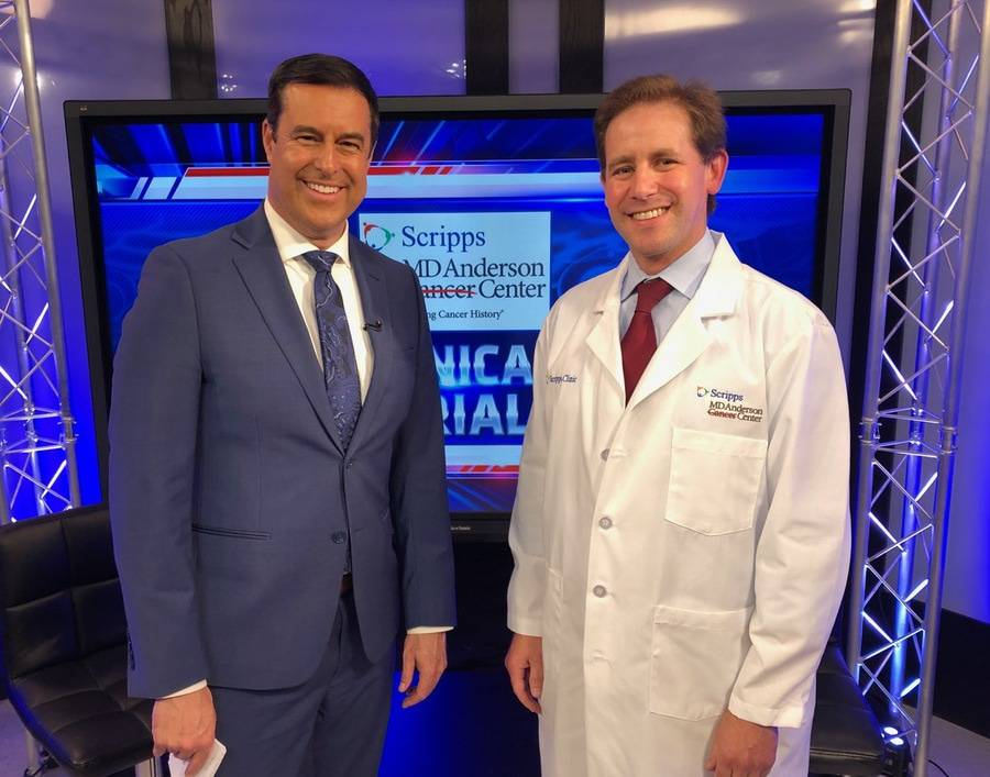A San Diego news anchor and Scripps oncologist smile for a photo during a news segment recording.