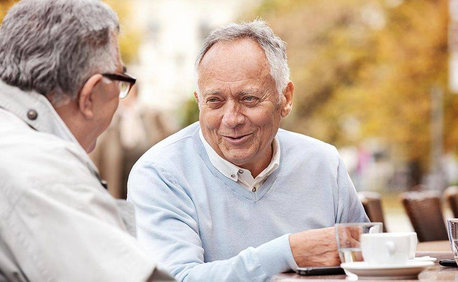A smiling mature man having coffee with a friend represents the importance of lung cancer screening and prevention.