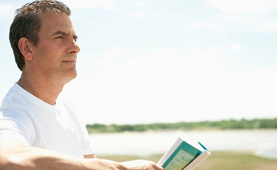 A middle-aged man by the shoreline represents the full life that can be led after lung cancer treatment.
