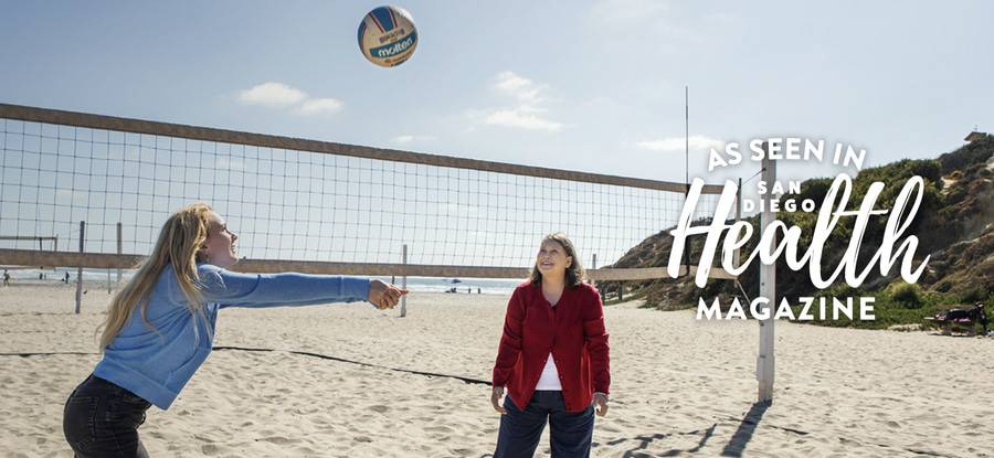 Mother and her daughter playing volleyball on the beach in San Diego.