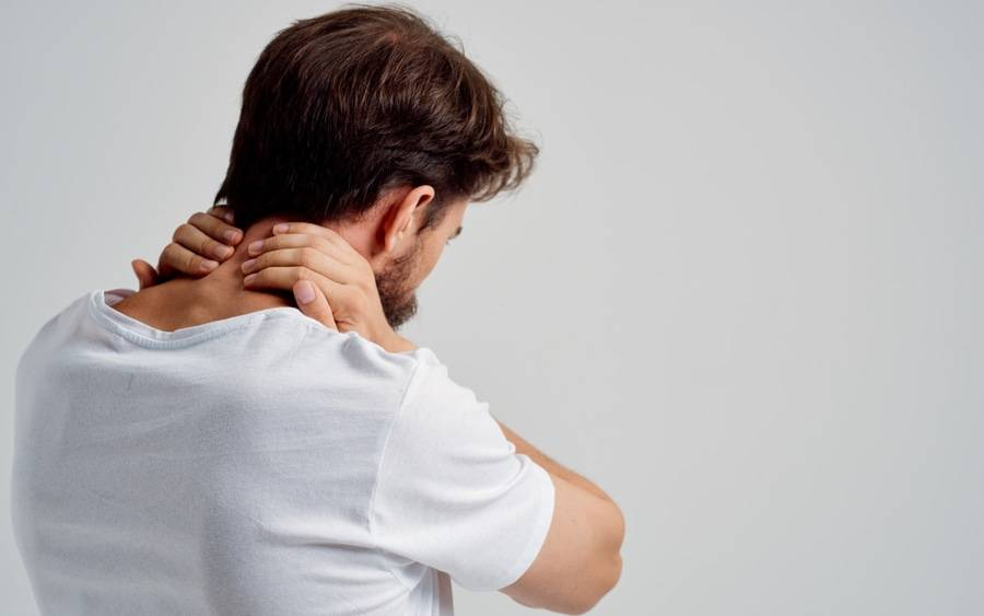 Man with neck pain rubs his neck