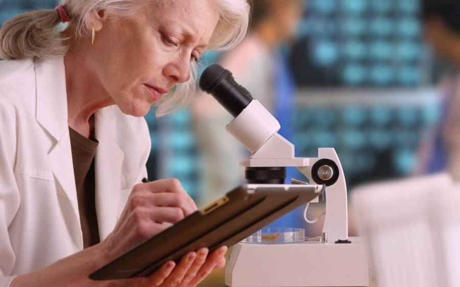 An older clinical employee takes notes while doing work in laboratory.