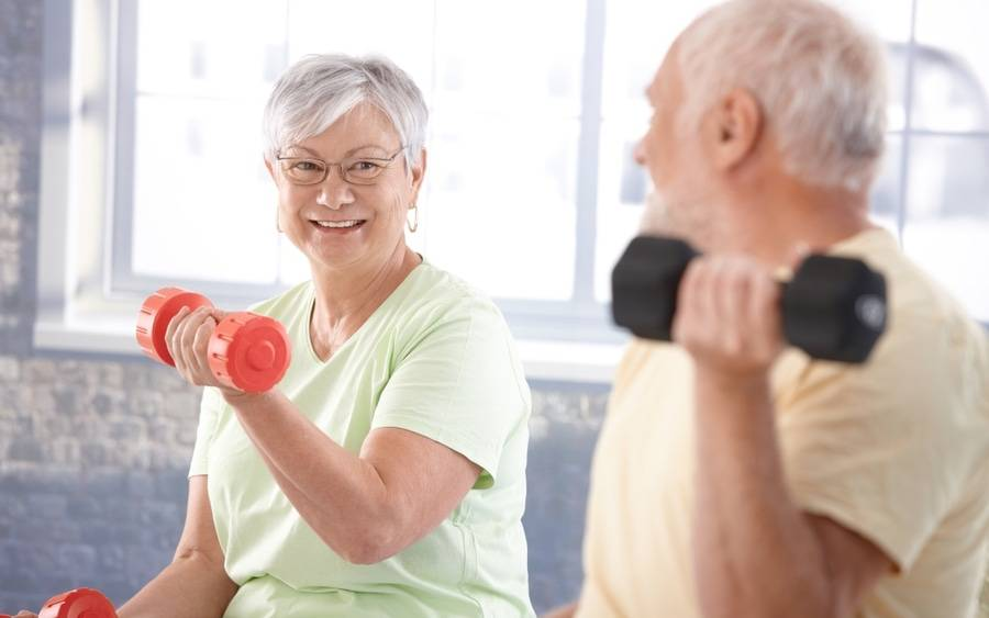 Older couple doing light weights as part of cardiac rehab program.