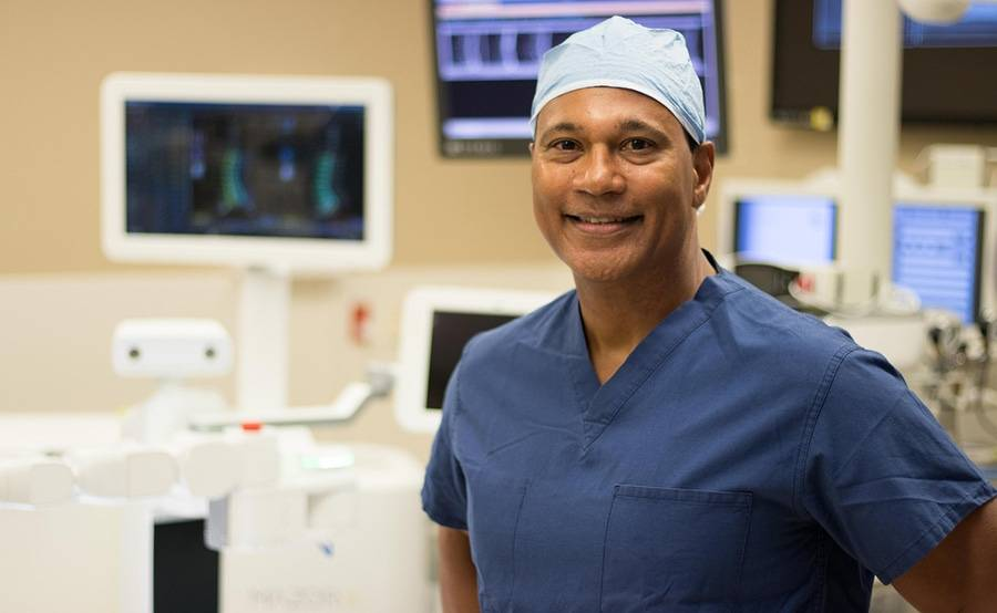 Spine surgeon Neville Alleyne, MD, smiles while standing in the Mazor X spine surgery suite.