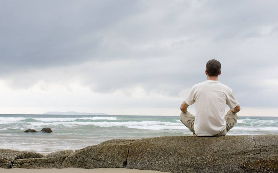 A man sits on a rock by the beach, practicing mindfulness-based stress reduction.