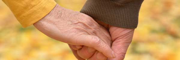 Close up shot of an elderly man and woman holding hands in an outdoor autumn setting