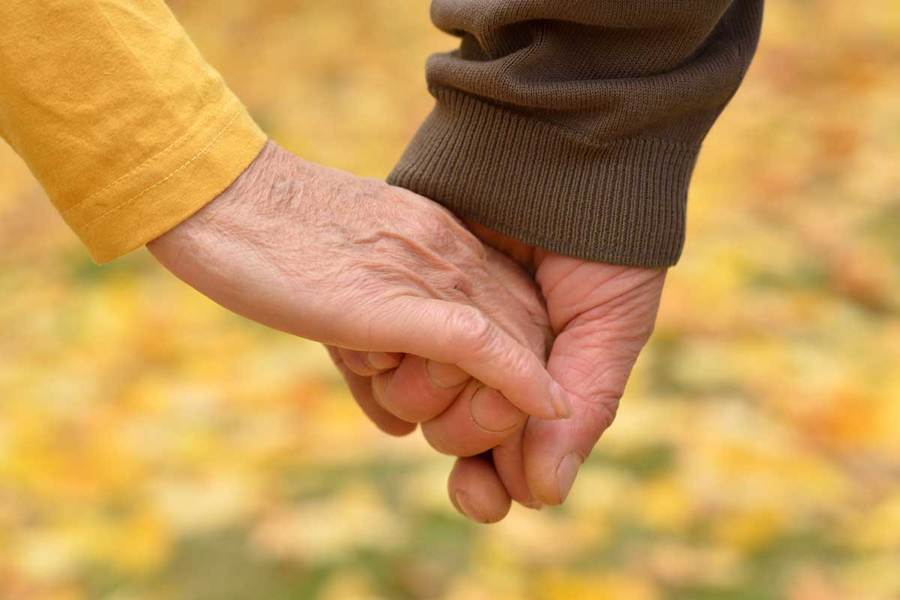 Close up shot of elderly man and woman holding hands in an outdoor autumn setting.