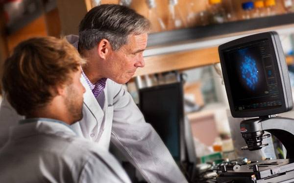 Two male Scripps Researchers view a microscopic image, work that may be impacted by possible NIH budget cuts.