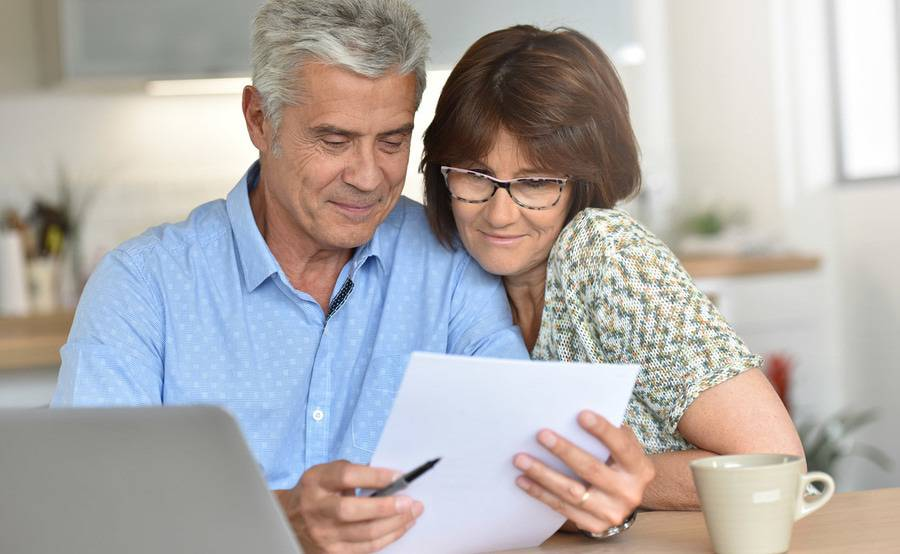 A mature couple reviews paperwork together, representing the important decisions around Medicare enrollment when you turn 65.