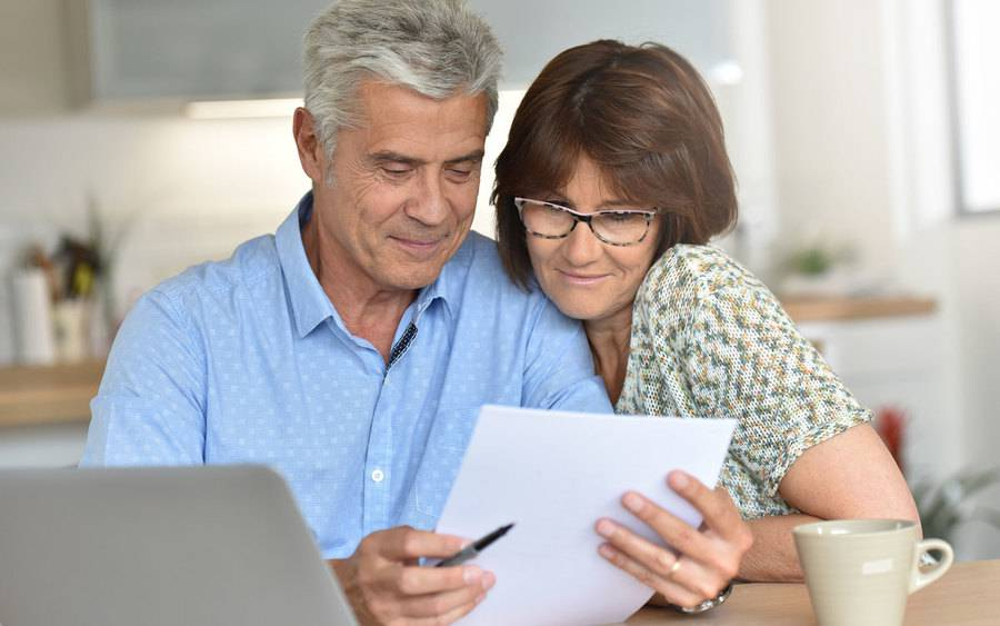 Older couple in their home near a computer over looking some paperwork.