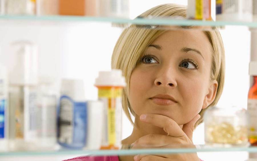 A woman peers into a medicine cabinet filled with prescriptions and beauty items.