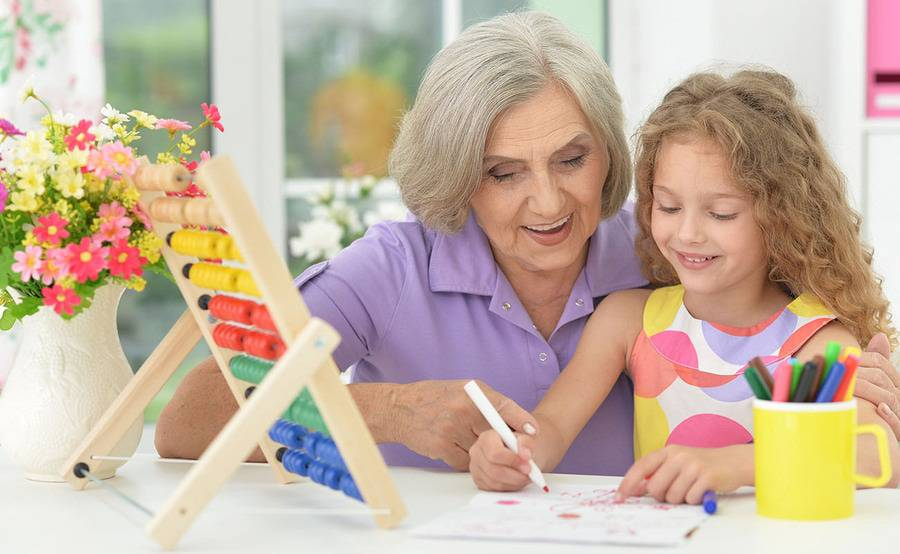 A mature woman colors with her granddaughter, representing a healthier life with treatment for mesenteric ischemia or thrombosis.