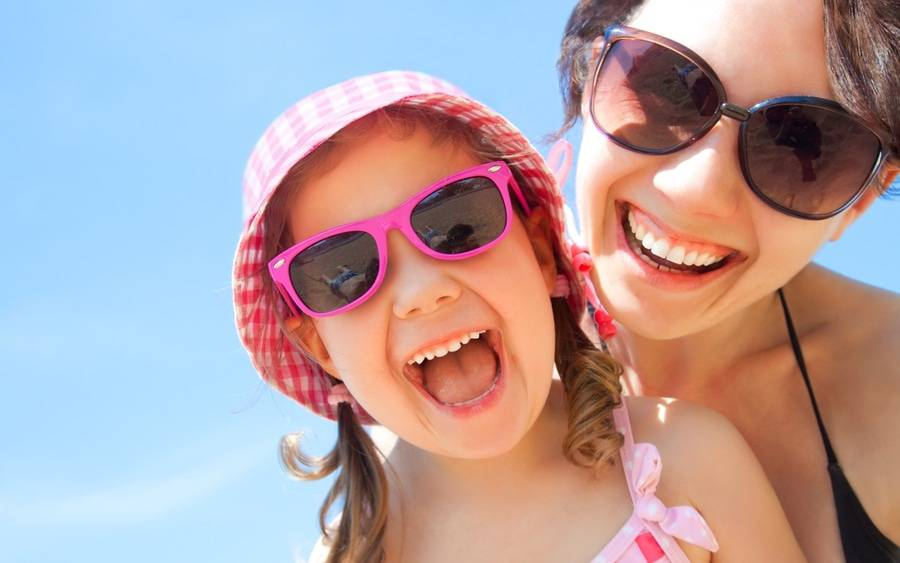 Mother and daughter wearing shades and laughing at the beach.