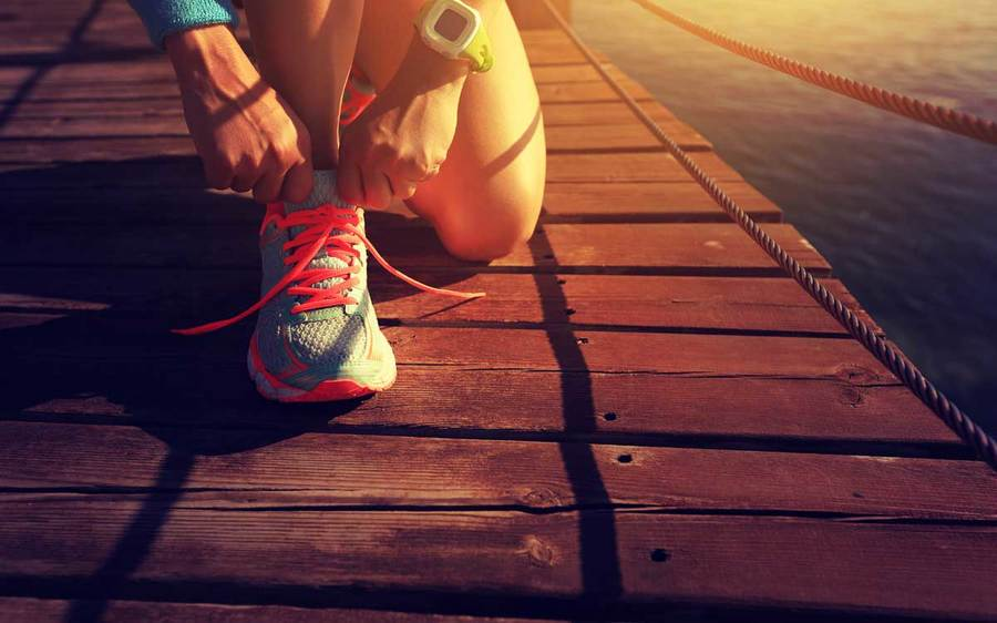 Close up view of an athlete tying her running shoes on a wooden pier