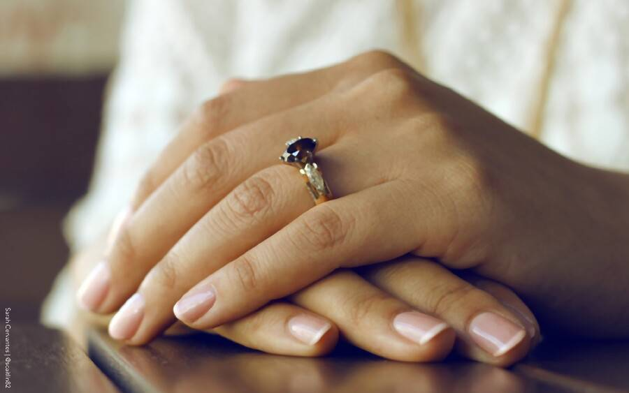 Woman wearing ring showing off her healthy nails.