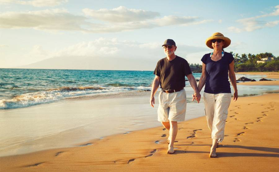 A mature couple walks down the beach, representing the successful management of kidney disease by Scripps nephrologists.