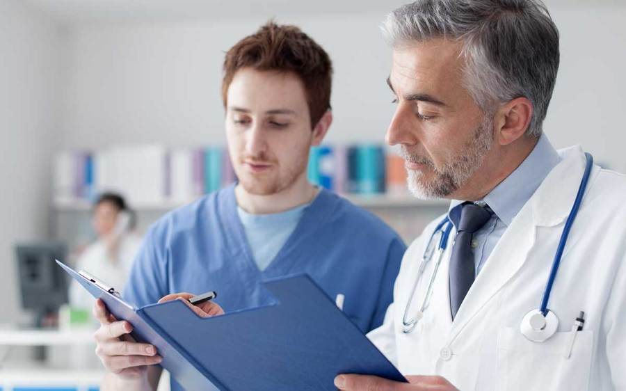 A doctor and physician look at a clipboard in a clinical setting