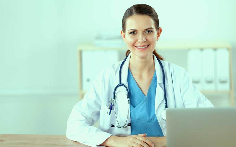 A smiling physician wearing a stethoscope pauses while working on a laptop in a clinical office environment.