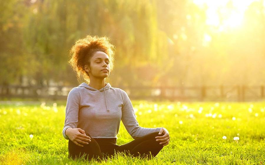 A woman meditates in a grassy field on a sunny day.