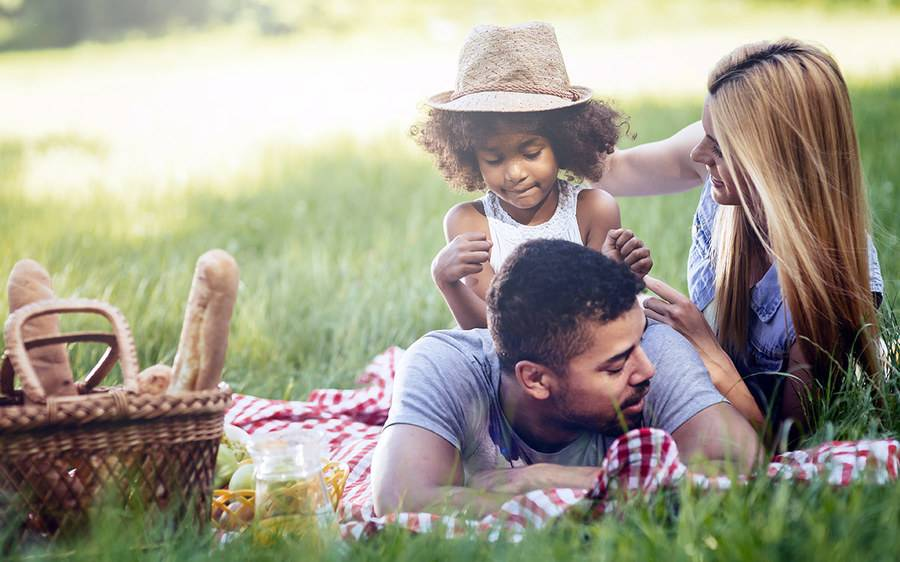 A family of three having a picnic in the shade on a sunny day.