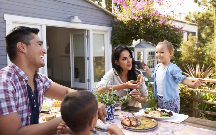 A young family enjoy a healthy meal in their yard, comprising fall food advice offered by a Scripps diabetes expert.