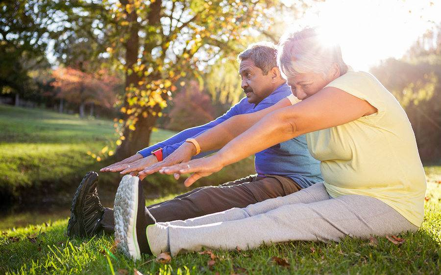 A couple stretches their legs before exercising together outdoors.
