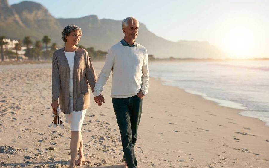A male stoke survivor strolls the beach with his wife after a landmark NIH study on stroke prevention proves effective.