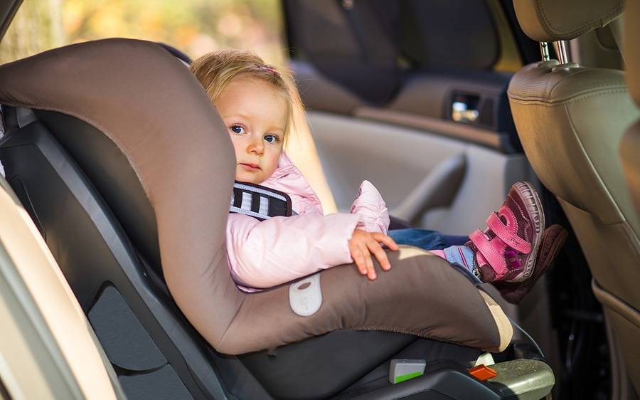 A toddler girl in a pink jacket is safely strapped in her car seat in the back seat of a car.