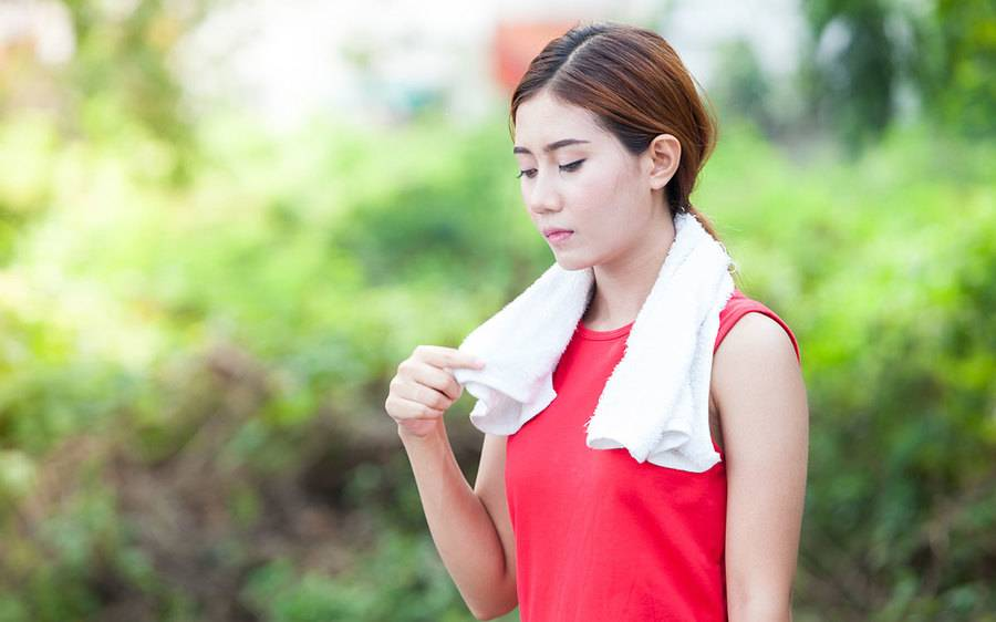 A woman holding a towel finishes exercising.