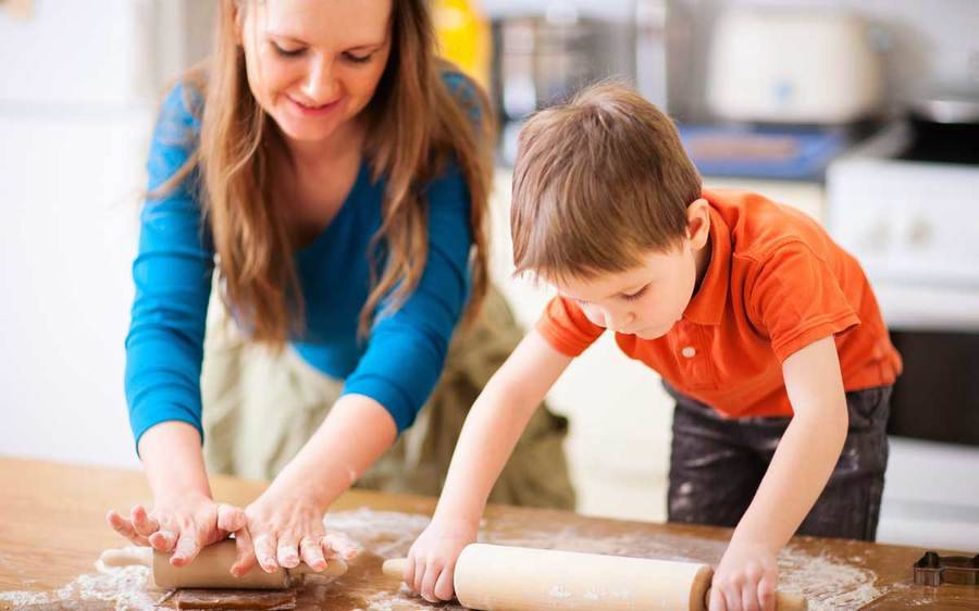 A mother and your young son roll out dough in the kitchen as one of five ways to manage holiday stress.